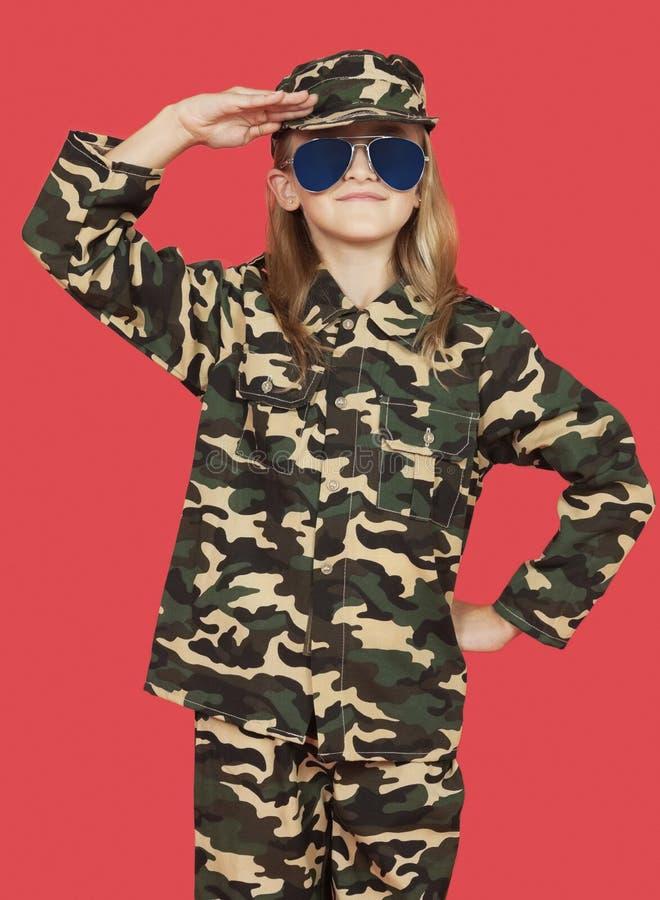 Portrait de la jeune fille dans l'uniforme militaire saluant sur le fond rouge images stock