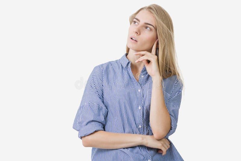 Portrait de la jeune fille européenne blonde utilisant la chemise rayée bleue pensant à quelque chose au-dessus du fond blanc photographie stock