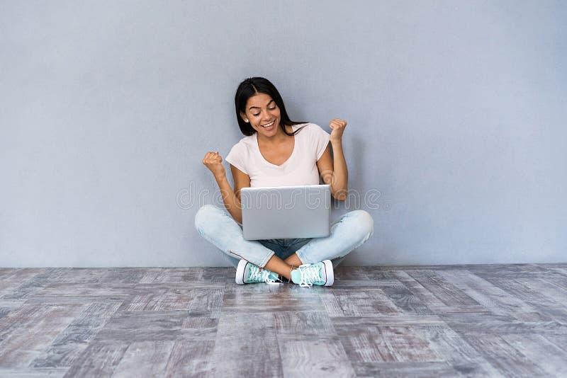 Portrait de la jeune fille occasionnelle enthousiaste célébrant le succès tout en se reposant avec l'ordinateur portable d'isolem photo stock