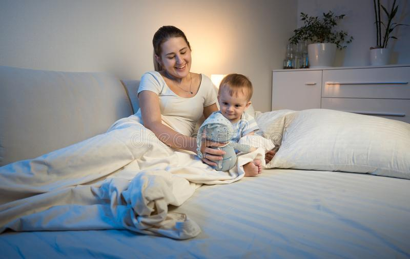 Portrait de la jeune mère de sourire jouant avec son bébé garçon avec le jouet de peluche images libres de droits