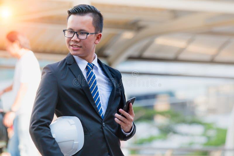 Portrait de la jeune main moderne sûre de costume de noir d'usage d'homme d'affaires tenant le comprimé numérique photographie stock