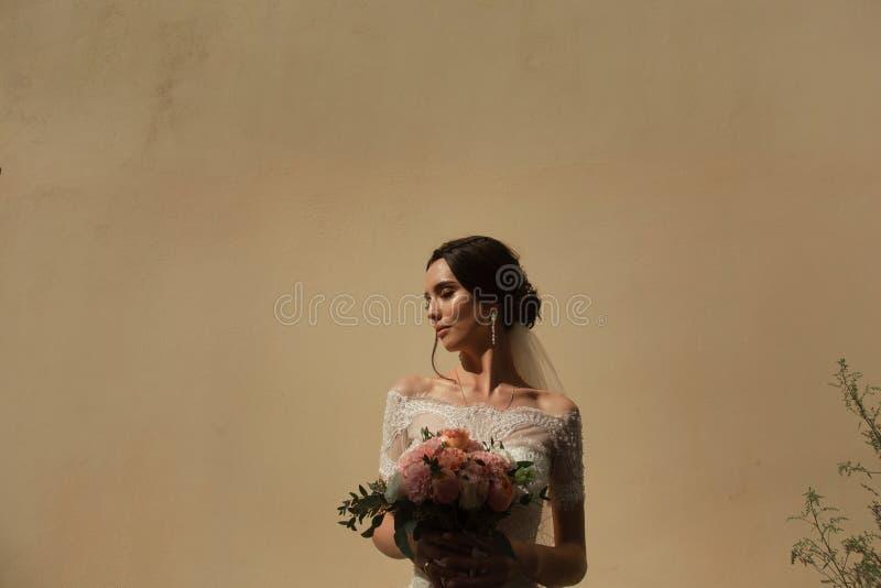 Portrait de la jeune mariée avec un groupe de fleurs sur le fond du mur photos libres de droits