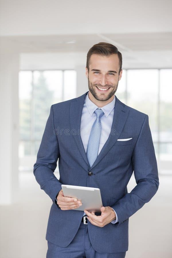 Portrait de la jeune position belle d'homme d'affaires avec le comprimé numérique dans le nouveau bureau photo stock
