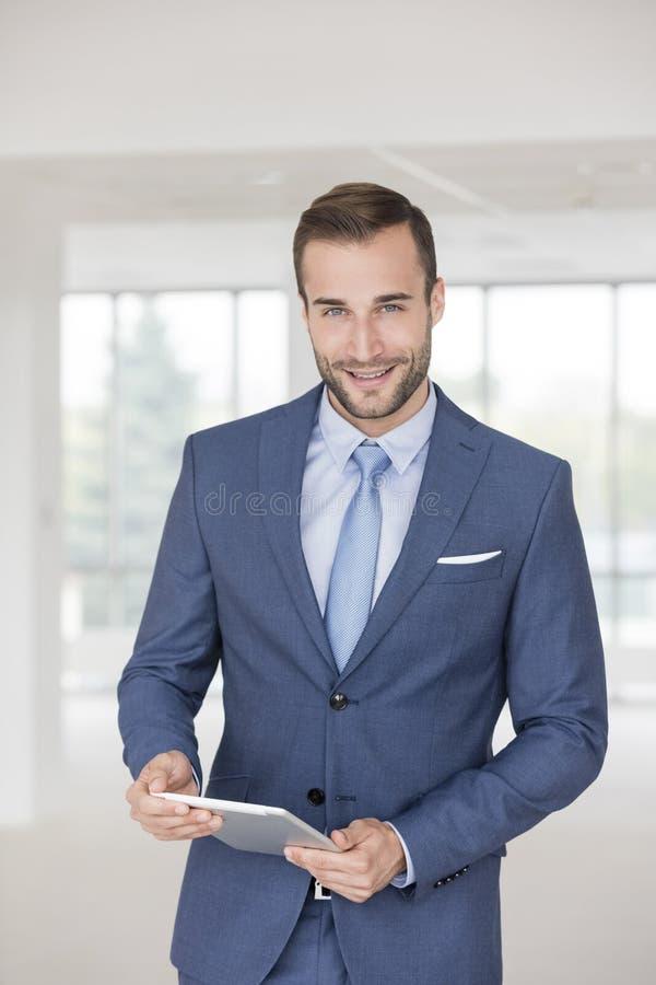Portrait de la jeune position belle sûre d'homme d'affaires avec le comprimé numérique dans le nouveau bureau photo libre de droits