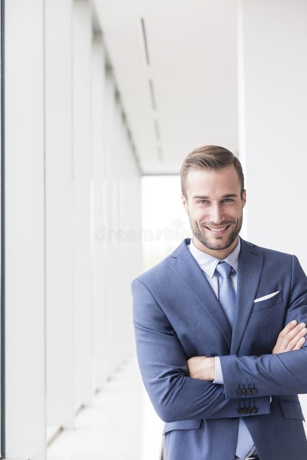 Portrait de la jeune position belle de sourire d'homme d'affaires avec des bras croisés dans le nouveau bureau photographie stock
