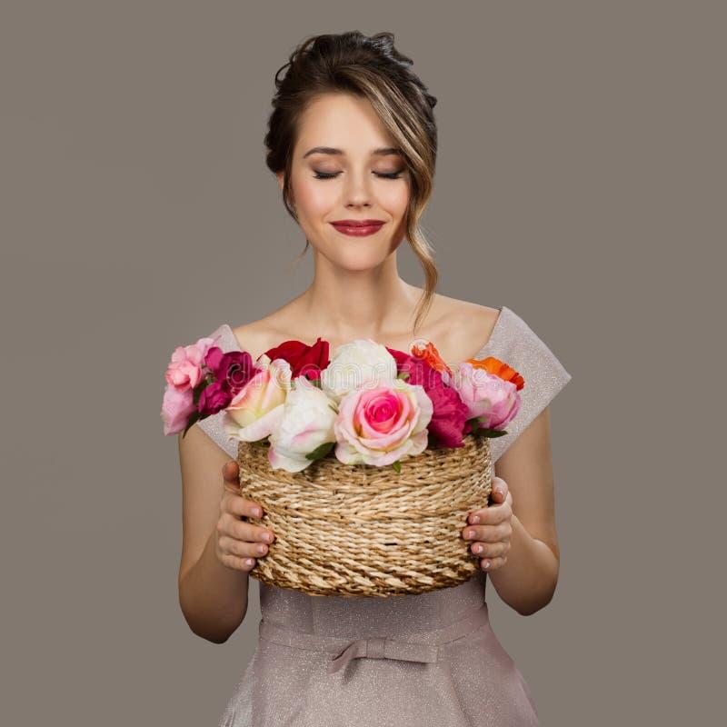 Portrait de la jolie femme de sourire tenant des fleurs images stock
