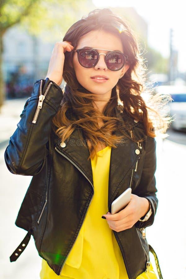 Portrait de la jolie fille de brune posant à la caméra dans des lunettes de soleil sur la rue dans le matin ensoleillé Elle utili photo libre de droits