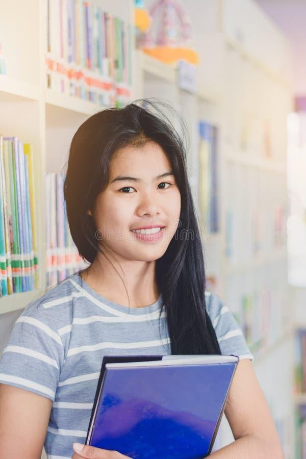 Portrait de la lecture d'étudiant et de la recherche asiatiques intelligentes de faire photo libre de droits