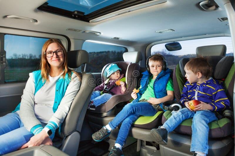 Portrait de la mère et de trois garçons s'asseyant dans une voiture photo stock
