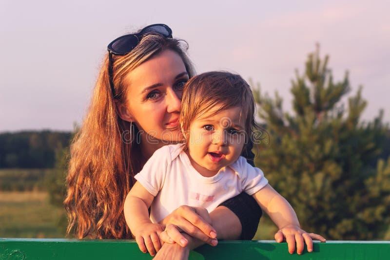 Portrait de la mère et du petit bébé étreignant au coucher du soleil images libres de droits