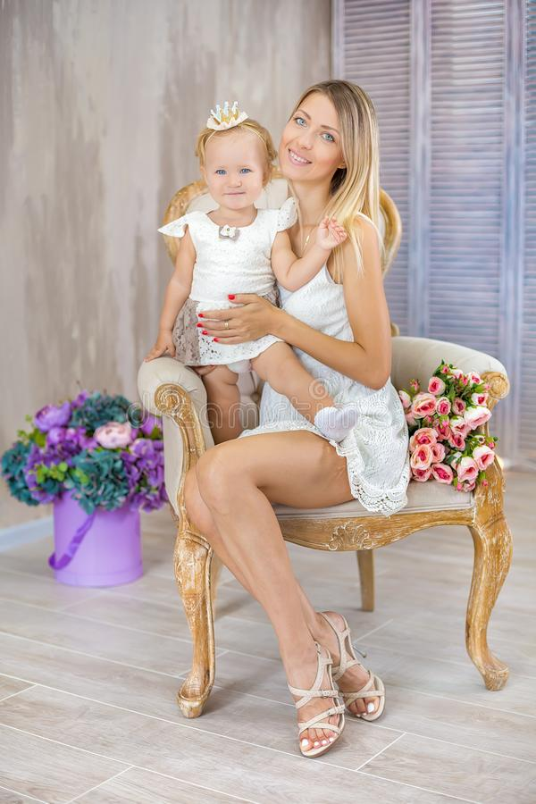 Portrait de la mère et de la fille belles s'étreignant posant sur la rétro chaise avec le bouquet des fleurs photographie stock libre de droits
