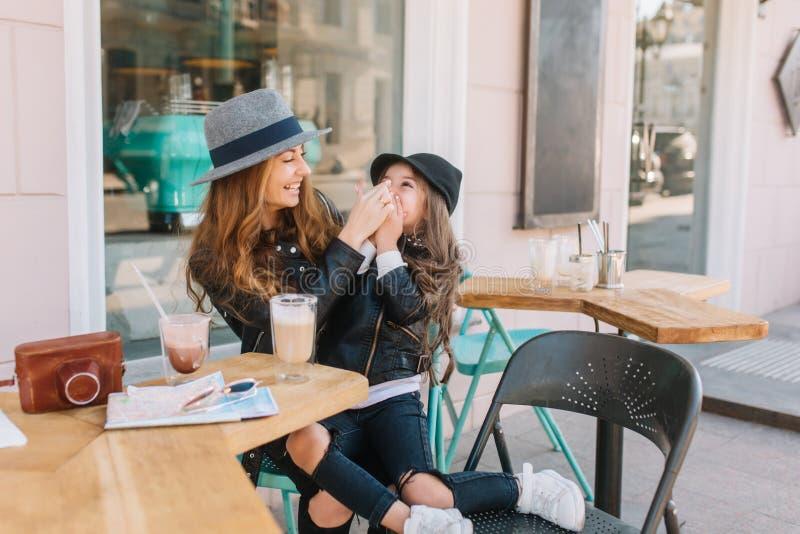 Portrait de la mère et de la fille prenant le déjeuner au café extérieur après l'achat Jeune femme gaie dans l'alimentation éléga images libres de droits