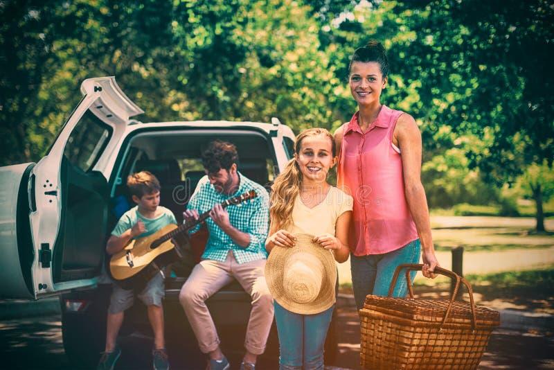 Portrait de la mère et de la fille se tenant avec le panier de pique-nique tandis que père et fils jouant la guitare à b photo libre de droits