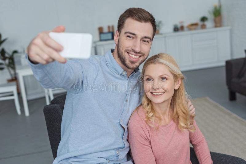 portrait de la mère de sourire et du fils développé prenant le selfie sur le smartphone photos stock