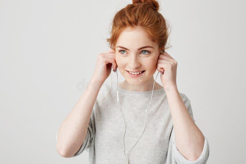 Portrait de la mise de sourire de jeune fille rousse gaie sur des écouteurs au-dessus du fond blanc image libre de droits