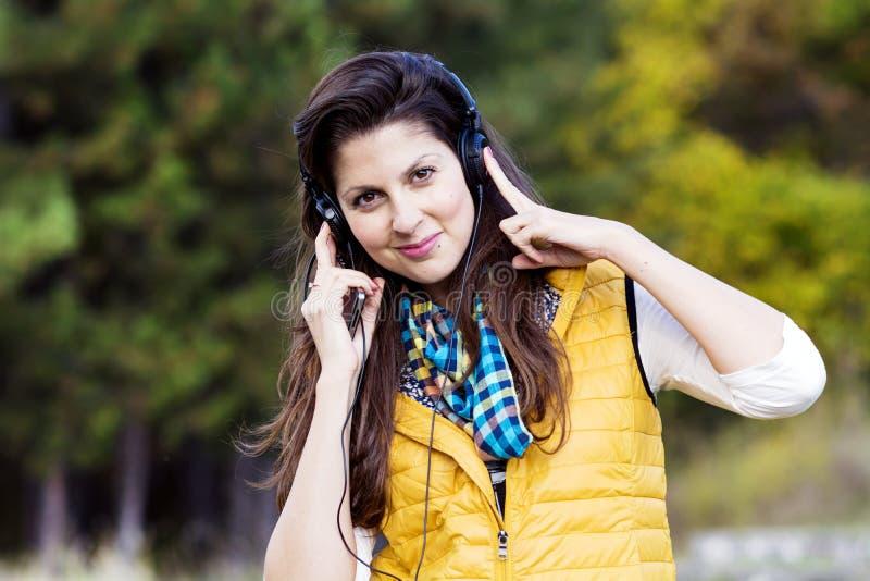 Portrait de la musique de écoute de belle jeune femme extérieure Apprécier la musique photos libres de droits
