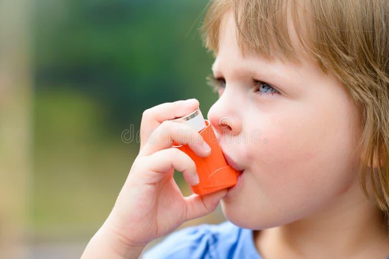 Portrait de la petite fille à l'aide de l'inhalateur d'asthme dehors photos libres de droits
