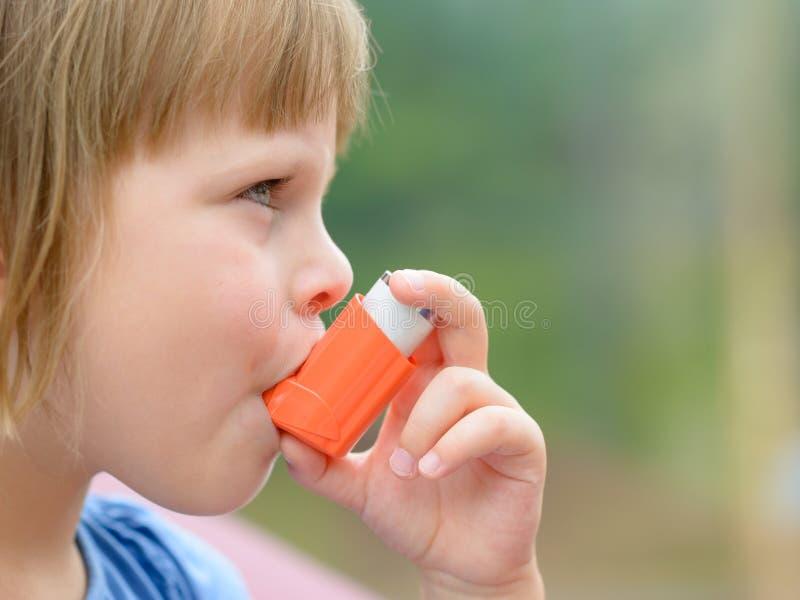 Portrait de la petite fille à l'aide de l'inhalateur d'asthme dehors images stock