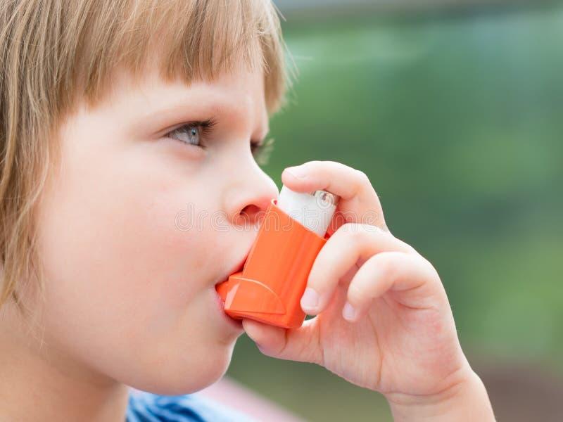 Portrait de la petite fille à l'aide de l'inhalateur d'asthme dehors photo libre de droits