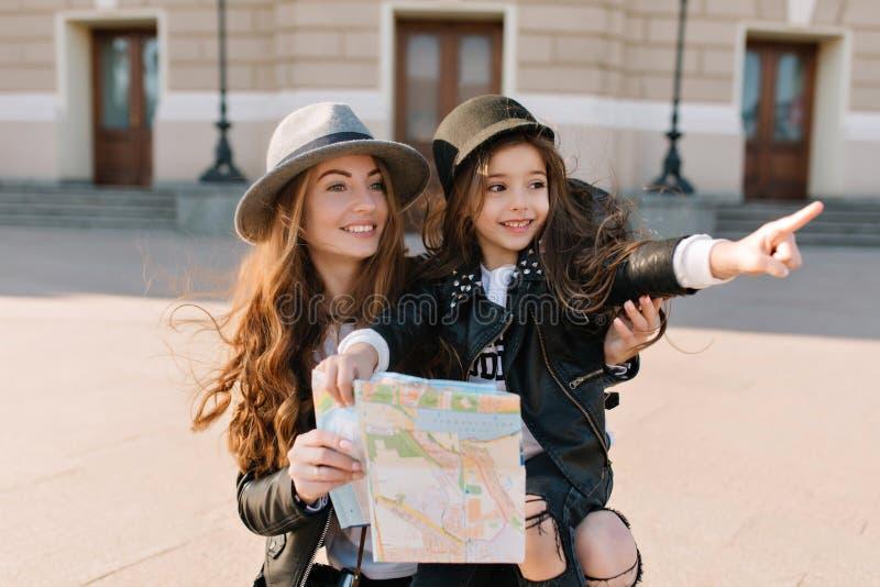 Portrait de la petite fille adorable dans le chapeau à la mode se dirigeant avec le doigt aux vues dans la nouvelle ville pendant images stock