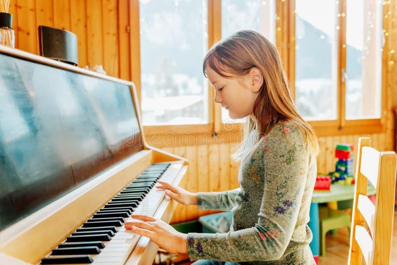 Portrait de la petite fille adorable jouant le piano images stock
