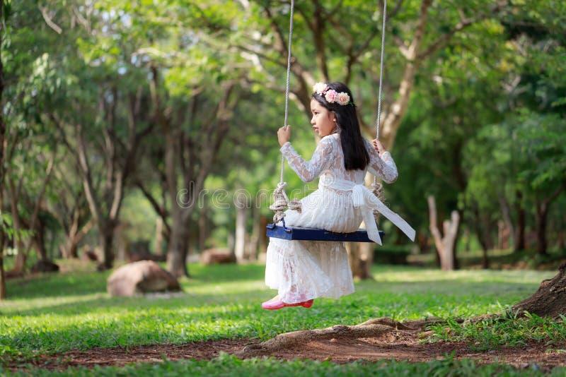 Portrait de la petite fille asiatique jouant l'oscillation sous le grand arbre dans la profondeur de foyer choisi de forêt de nat images stock