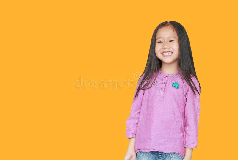 Portrait de la petite fille asiatique de sourire d'enfant d'isolement sur le fond jaune avec l'espace de copie Concept de sourire images stock