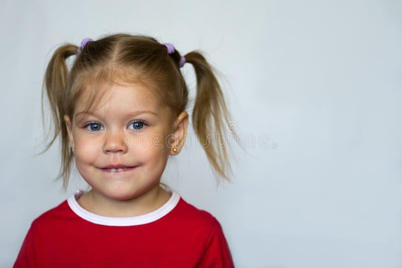 Portrait de la petite fille avec des yeux bleus mordant la lèvre inférieure regardant la caméra photographie stock