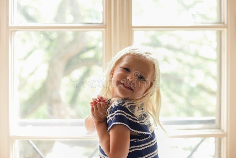 Portrait de la petite fille blonde s'asseyant dans l'intention ensoleillée de fenêtre image stock