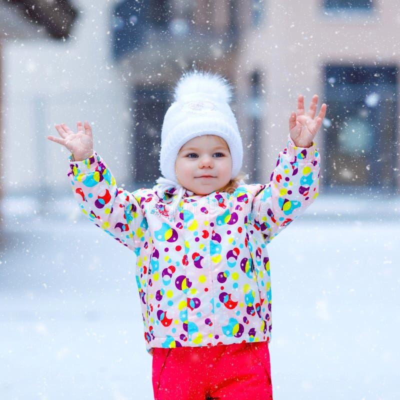 Portrait de la petite fille d'enfant en bas ?ge marchant dehors en hiver Enfant en bas ?ge mignon mangeant la sucrerie douce de l photo stock