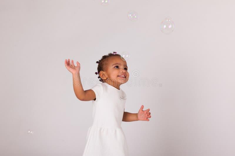 Portrait de la petite fille de petit Afro-américain jouant avec le soa photos libres de droits