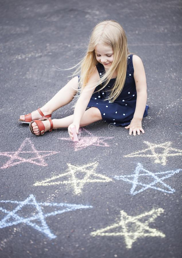Portrait de la petite fille heureuse s'asseyant sur l'asphalte et le dessin images libres de droits