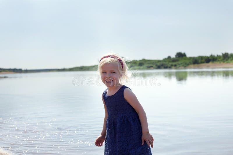 Portrait de la petite fille heureuse se reposant au lac image stock