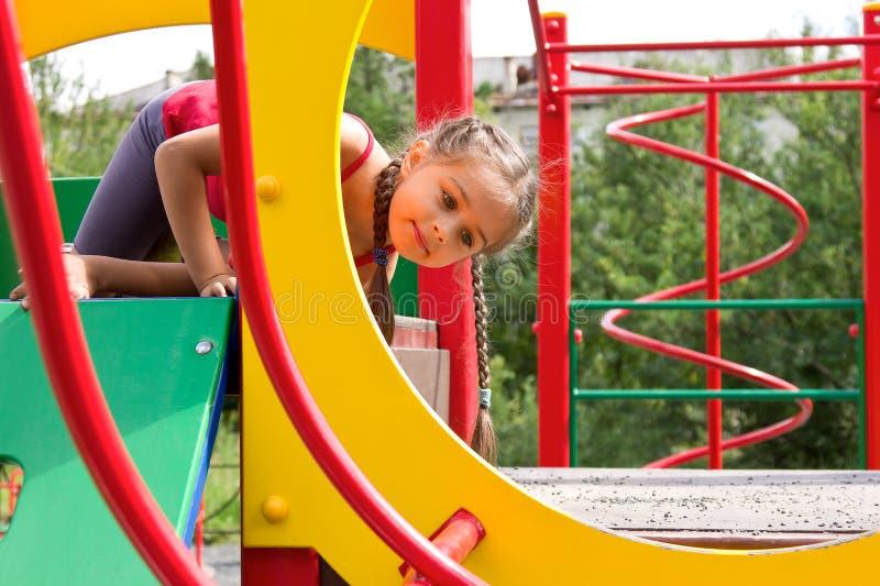 Portrait de la petite fille mignonne jouant sur le terrain de jeu photos libres de droits