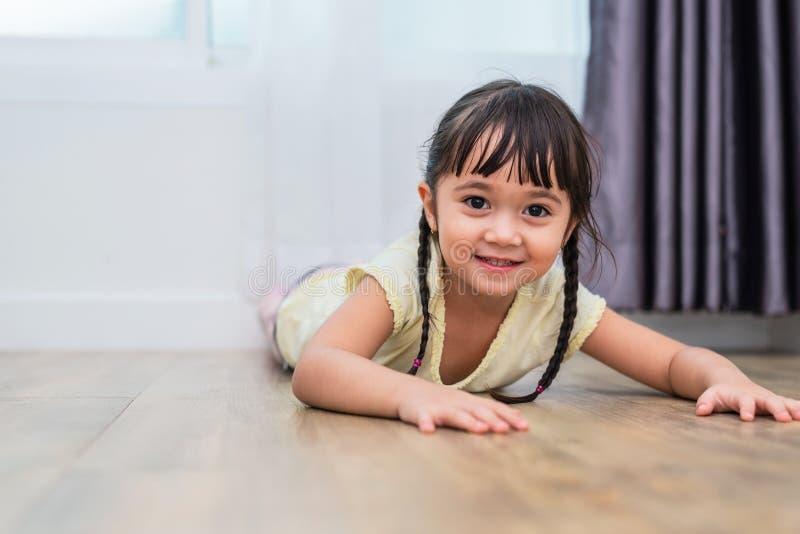 Portrait de la petite fille mignonne se trouvant sur le plancher avec la caméra aux pieds nus et regardante à la maison Concept d photos stock