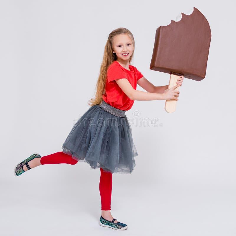 Portrait de la petite fille mignonne tenant la crème glacée énorme au-dessus du blanc image libre de droits
