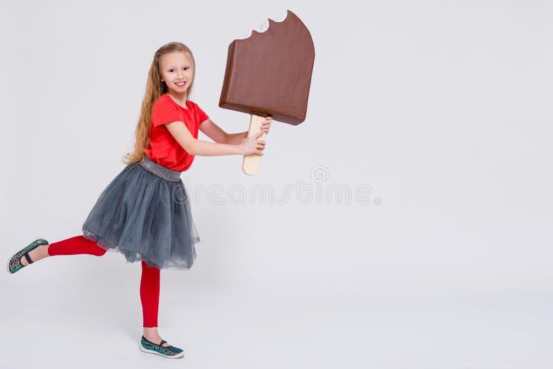 Portrait de la petite fille mignonne tenant la crème glacée et l'espace énormes de copie au-dessus du blanc images libres de droits