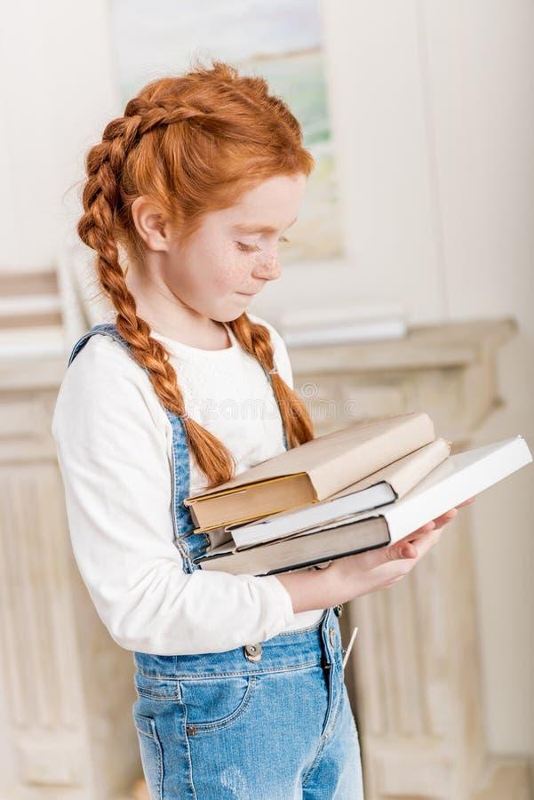 Portrait de la petite fille rousse adorable tenant la pile des livres image libre de droits