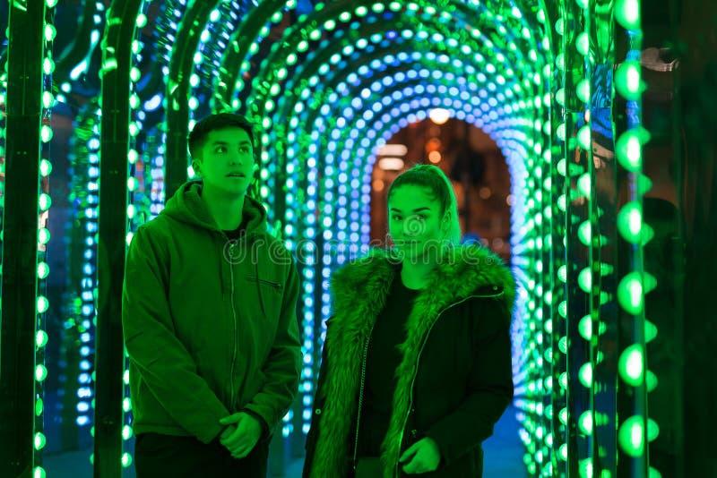 Portrait de la position adolescente de frère et de soeur de métis dans la lampe au néon verte images stock