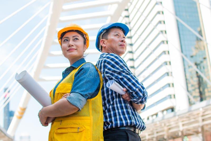 Portrait de la position et du regard d'ingénieur industriel d'associés d'équipe au casque de sécurité d'usage de caméra image stock