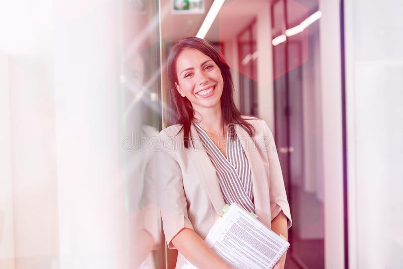 Portrait de la position heureuse de femme d'affaires avec des documents par le mur au bureau photo stock