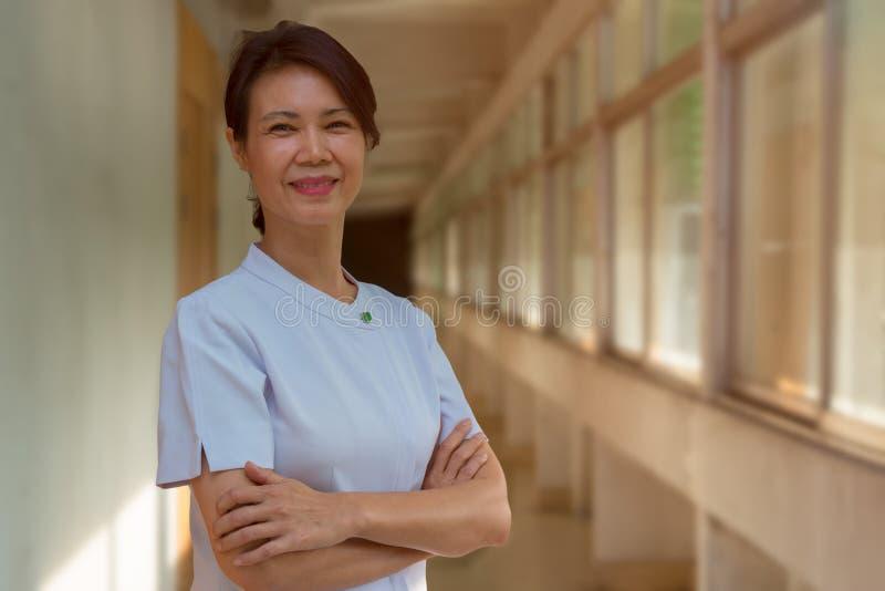 Portrait de la position plus ancienne de sourire d'infirmière au balcon d'hôpital photographie stock