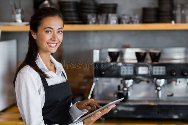 Portrait de la serveuse de sourire à l'aide du comprimé numérique photographie stock libre de droits