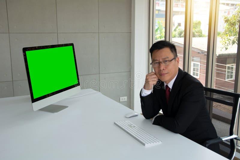 Portrait de la signalisation de sourire d'homme d'affaires dans l'écran vide avant avec le clavier et la souris image stock