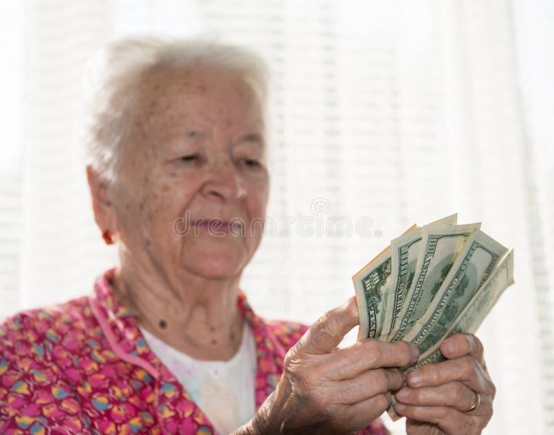 Portrait de la vieille femme aux cheveux gris tenant des dollars dans des mains photographie stock