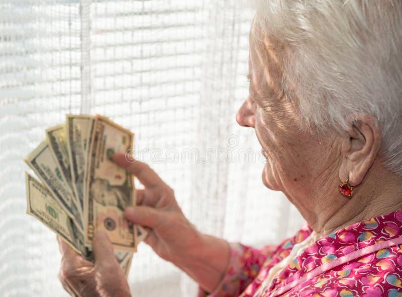 Portrait de la vieille femme aux cheveux gris tenant des dollars dans des mains images stock