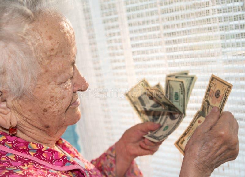 Portrait de la vieille femme aux cheveux gris tenant des dollars dans des mains photographie stock libre de droits