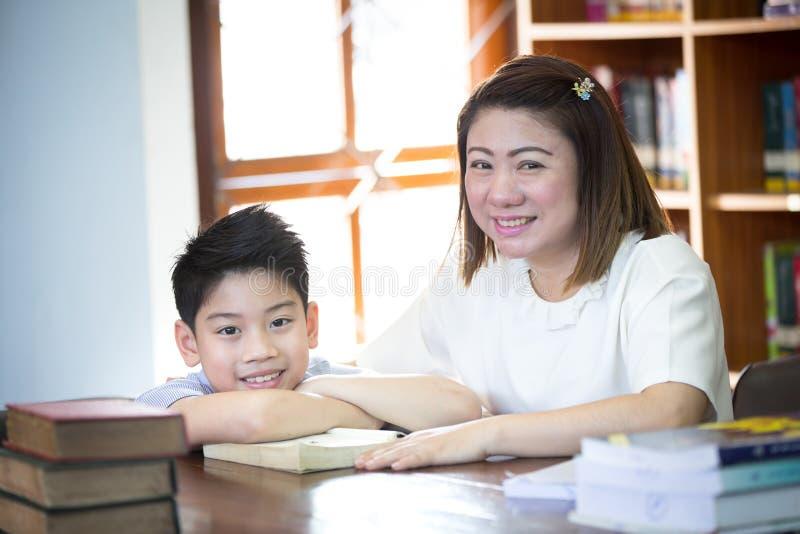 Portrait de livre de lecture heureux de garçon et de professeur par l'étagère dans l images stock
