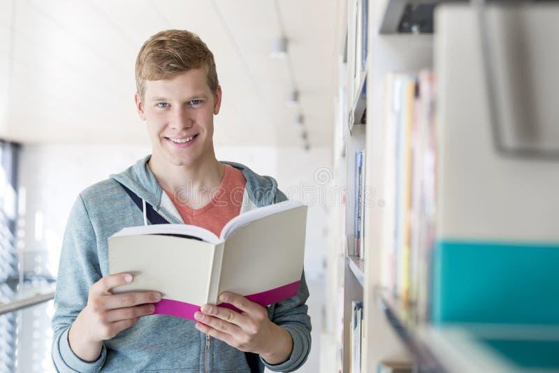 Portrait de livre de lecture de sourire d'étudiant à la bibliothèque à l'université photo stock