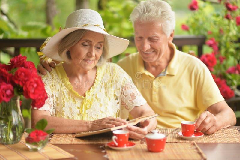 Portrait de livre de lecture sup?rieur heureux de couples tout en buvant du caf? photographie stock libre de droits